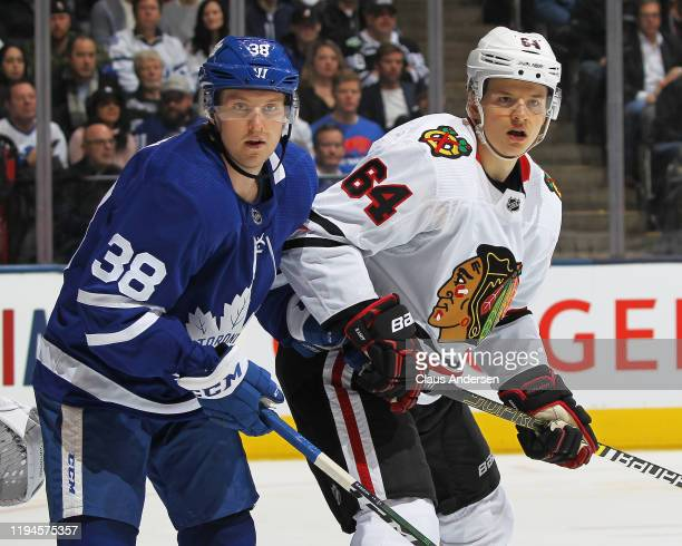 David Kampf of the Chicago Blackhawks skates against Rasmus Sandin of the Toronto Maple Leafs during an NHL game at Scotiabank Arena on January 18...