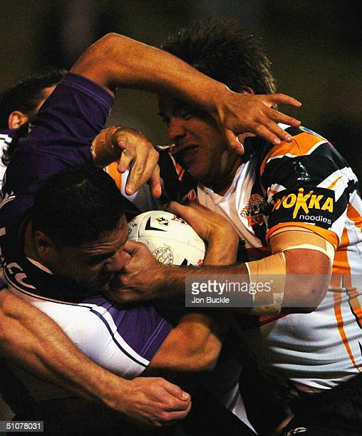 David Kidwell of the Storm is tackled by John Skandalis of the Tigers during the NRL round 19 match between the Wests Tigers and Melbourne Storm at...