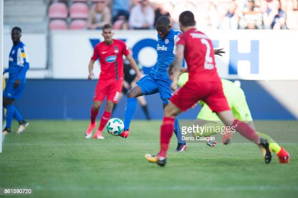 David Kinsombi of Kiel scores his team's fourth goal against Marnon Busch and goalkeeper Kevin Mueller of Heidenheim during the Second Bundesliga...