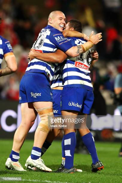 David Klemmer and Adam Elliott of the Bulldogs celebrates with Ofahiki Ogden of the Bulldogs after he scored a try during the round 24 NRL match...