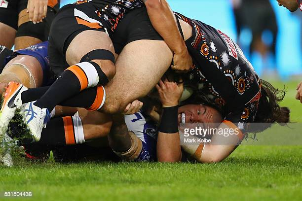 David Klemmer of the Bulldogs is held up over the line by Aaron Woods of the Tigers during the round 10 NRL match between the Wests Tigers and the...