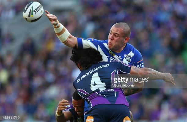 David Klemmer of the Bulldogs passes the ball whilst being tackled by Mahe Fonua of the Storm during the NRL 2nd Elimination Final match between the...