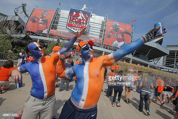 David Kline left and Chris Dominguez both of Colorado pose outside of the stadium while wearing blue and orange body paint before a game between the...
