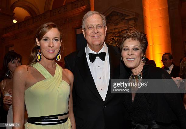 David Koch executive vice president of chemical technology for Koch Industries Inc center and wife Julia Flesher left stand for a photograph with a...