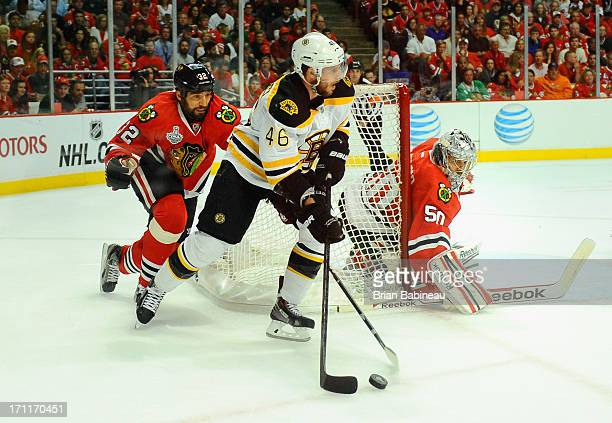 David Krejci of the Boston Bruins controls the puck away from goaltender Corey Crawford and Michal Rozsival of the Chicago Blackhawks during the...