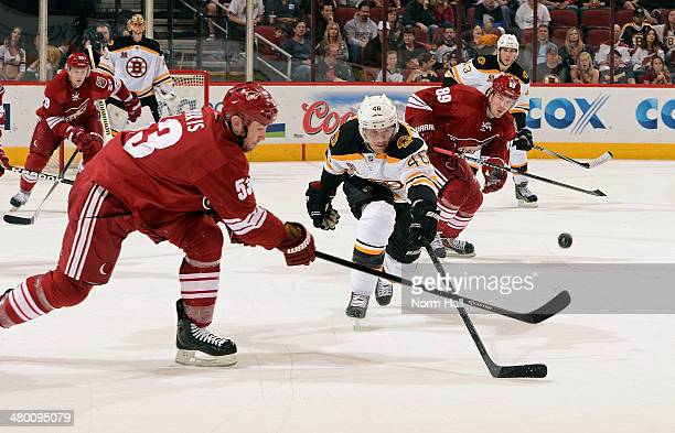 David Krejci of the Boston Bruins deflects a pass by Derek Morris of the Phoenix Coyotes during the first period at Jobing.com Arena on March 22,...