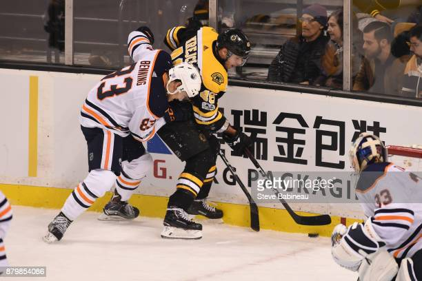 David Krejci of the Boston Bruins fight for the puck against Matt Benning of the Edmonton Oilers at the TD Garden on November 26 2017 in Boston...