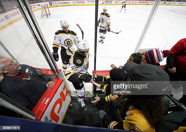 David Krejci of the Boston Bruins fist bumps a fan as he leaves the ice following the pregame warm up prior to NHL action against the Winnipeg Jets...