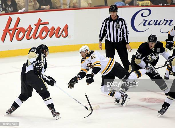 David Krejci of the Boston Bruins is checked by Evgeni Malkin of the Pittsburgh Penguins during Game Two of the Eastern Conference Final of the 2013...