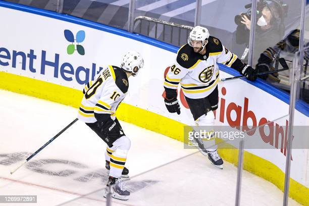 David Krejci of the Boston Bruins is congratulated by his teammate Anders Bjork after scoring a goal against the Tampa Bay Lightning during the third...