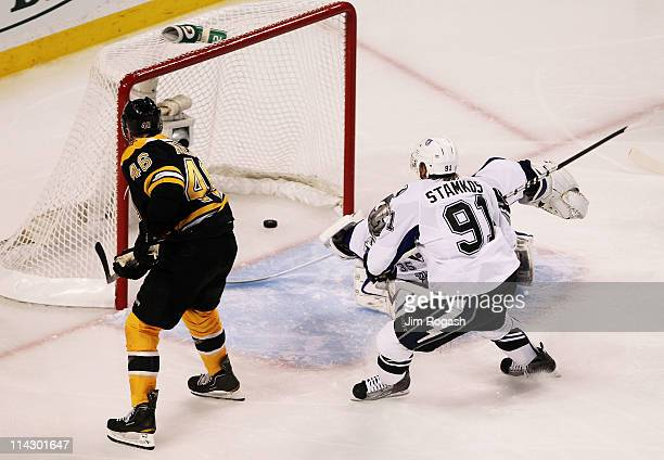 David Krejci of the Boston Bruins scores a second period goal past Steven Stamkos and Dwayne Roloson of the Tampa Bay Lightning in Game Two of the...