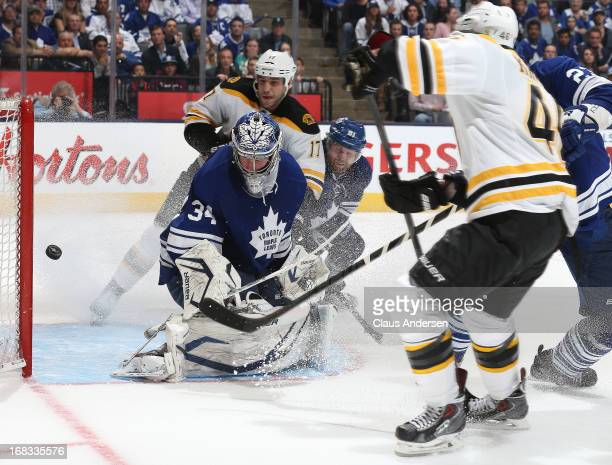 David Krejci of the Boston Bruins scores the overtime winning goal against James Reimer of the Toronto Maple Leafs in Game Four of the Eastern...