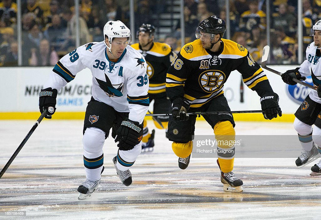 David Krejci #46 of the Boston Bruins skates up ice against Logan Couture #39 of the San Jose Sharks during the first period of an NHL hockey game on October 24, 2013 at TD Garden in Boston, Massachusetts.