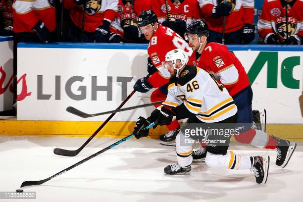David Krejci of the Boston Bruins skates with the puck against Colton Sceviour and Jamie McGinn of the Florida Panthers at the BBT Center on March 23...