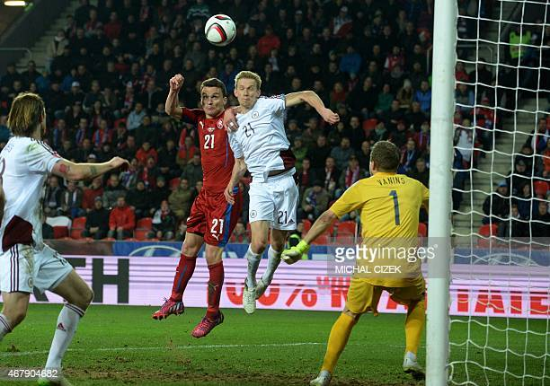 David Lafata of Czech Republic and Gints Freimanis of Latvia vie for the ball during the Group A Euro 2016 qualifying football match between Czech...