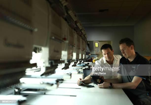 David Lambasa and Dan Garratt oversee the embroidery of the Coat of Arms of Australia while making the Kookaburra Australian Baggy Green Cap on...