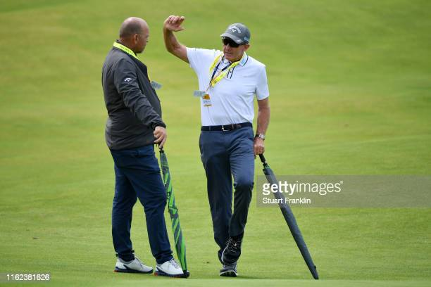David Ledbetter talks to Thomas Bjorn of Denmark during a practice round prior to the 148th Open Championship held on the Dunluce Links at Royal...