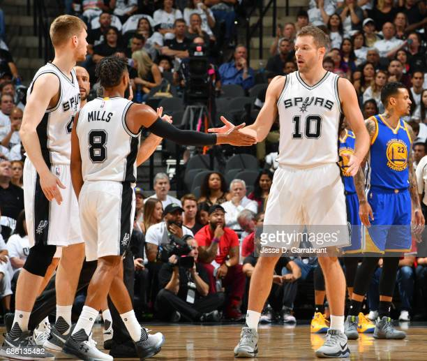 David Lee and Patty Mills of the San Antonio Spurs high five each other during the game against the Golden State Warriors during Game Three of the...
