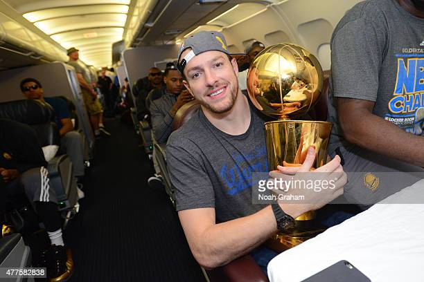 David Lee of the Golden State Warriors holds the NBA trophy on the plane as the team travels home from Cleveland after winning the 2015 NBA Finals on...