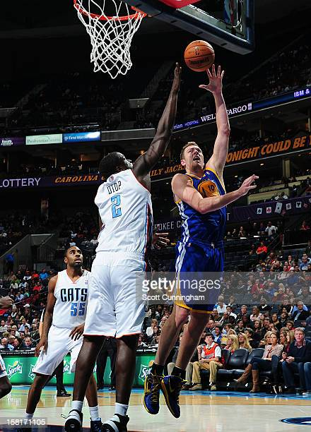 David Lee of the Golden State Warriors shoots against DeSagana Diop of the Charlotte Bobcats at Time Warner Cable Arena on December 10 2012 in...