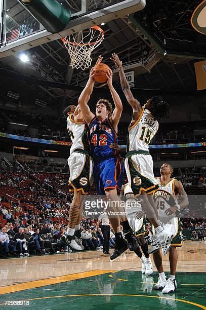 David Lee of the New York Knicks goes to the basket between the defense of Andre Brown and Mickael Gelable of the Seattle SuperSonics on January 5...