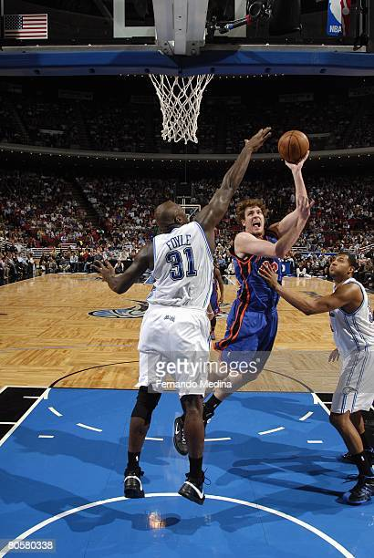 David Lee of the New York Knicks shoots against Adonal Foyle and Brian Cook of the Orlando Magic during the game at Amway Arena on March 1 2008 in...