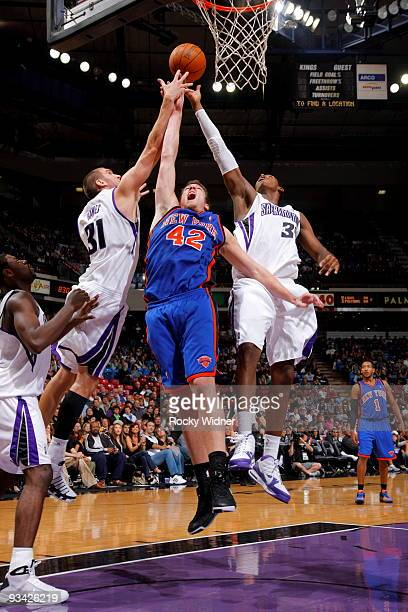 David Lee of the New York Knicks takes the ball to the basket against Spencer Hawes and Jason Thompson of the Sacramento Kings on November 25 2009 at...