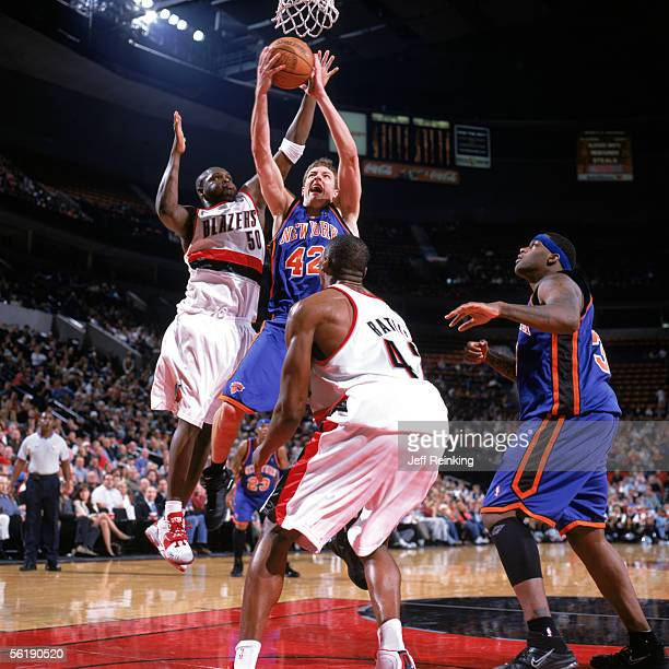 David Lee of the New York Knicks takes the ball to the basket between Zach Randolph and Theo Ratliff of the Portland Trail Blazers during a game at...