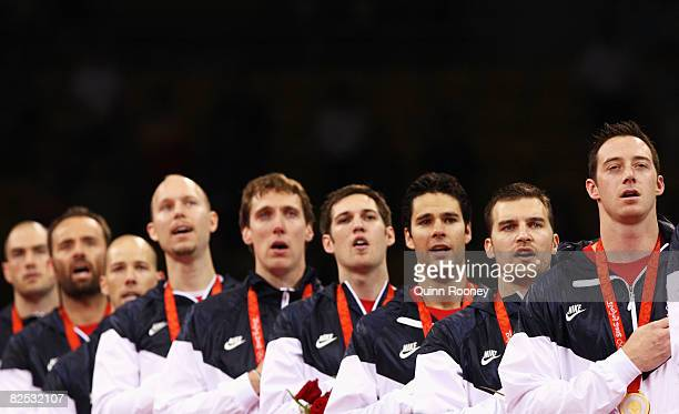 David Lee of the United States sings the national anthem on the podium with team mates after the Gold Medal volleyball match between the United...