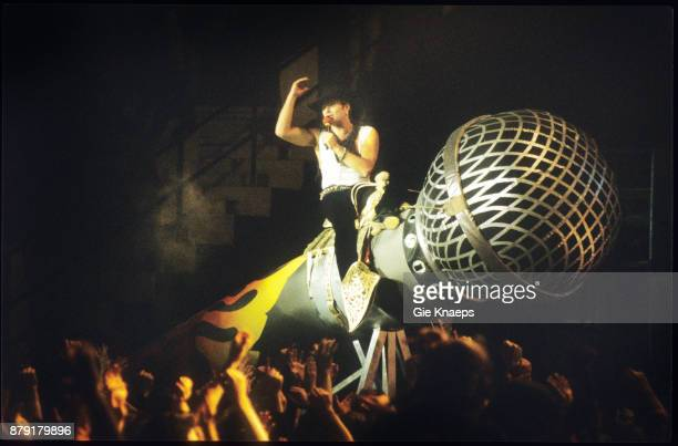 David Lee Roth riding on a giant model of a microphone performing on stage Vorst Nationaal Brussels Belgium 21st March 1991