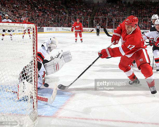 David Legwand of the Detroit Red Wings beats a diving Cory Schneider of the New Jersey Devils scoring his first goal since joining the team during an...