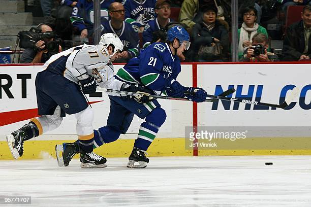 David Legwand of the Nashville Predators checks Mason Raymond of the Vancouver Canucks during their game at General Motors Place on January 11 2010...