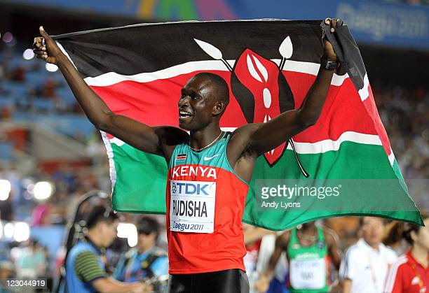 David Lekuta Rudisha of Kenya celebrates with his country's flag after claiming gold in the men's 800 metres final during day four of the 13th IAAF...