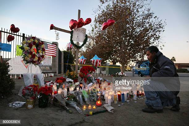 David Lem pays his respects at a memorial near the Inland Regional Center on December 5, 2015 in San Bernardino, California. Police continue to...