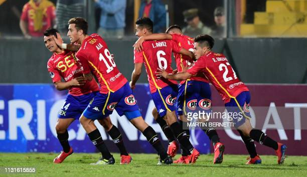 David Llanos of Chile's Union Espanola celebrates with Jose Aja and teammates after scoring against Ecuador's Mushuc Runa during their Copa...