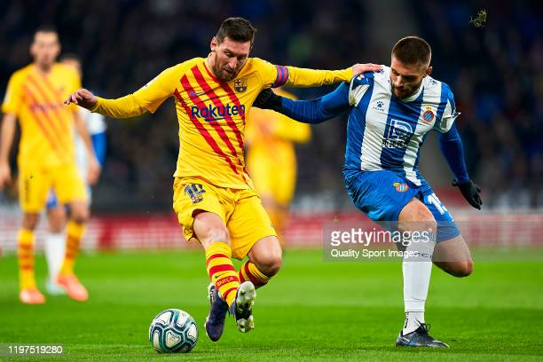 David Lopez of RCD Espanyol competes for the ball with Lionel Messi of FC Barcelona during the Liga match between RCD Espanyol and FC Barcelona at...