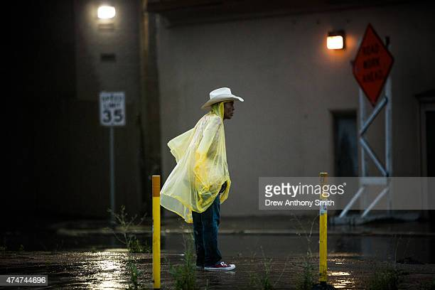 David Lopez waits to cross the street as rain falls on May 25 2015 in Austin Texas Texas Gov Greg Abbott toured the damage zone where one person is...