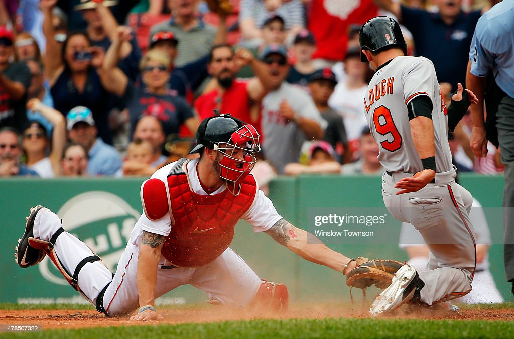 David Lough #9 of the Baltimore Orioles is tagged out at home by catcher Blake Swihart #23 of the Boston Red Sox while trying to score on a sacrifice fly during the ninth inning in a game at Fenway Park on June 25, 2015 in Boston, Massachusetts.
