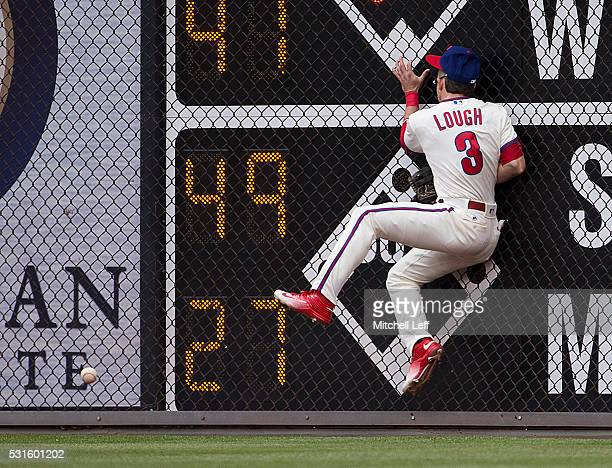 David Lough of the Philadelphia Phillies hits the wall trying to catch a ball hit by Jay Bruce of the Cincinnati Reds in the top of the second inning...