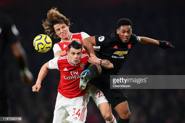 David Luiz and Granit Xhaka of Arsenal compete for the ball with Anthony Martial of Manchester United during the Premier League match between Arsenal...