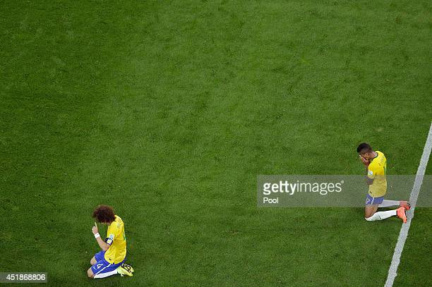 David Luiz and Luiz Gustavo of Brazil react after being defeated by Germany 71 during the 2014 FIFA World Cup Brazil Semi Final match between Brazil...