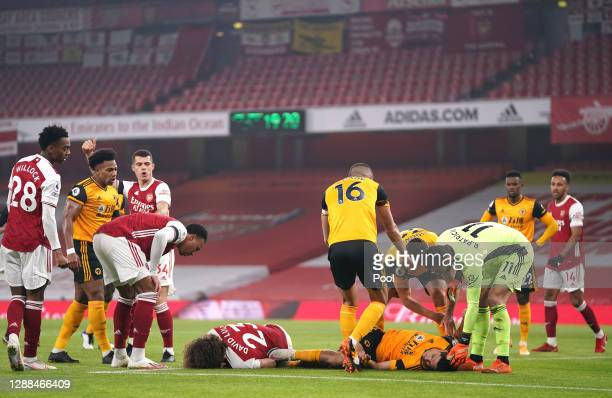 David Luiz of Arsenal and Raul Jimenez of Wolverhampton Wanderers lie injured after a collision during the Premier League match between Arsenal and...