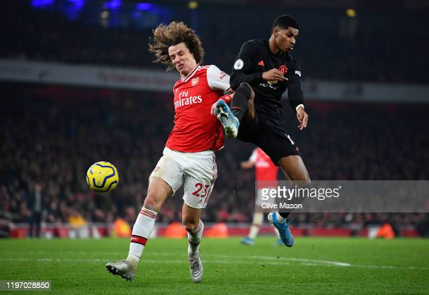 David Luiz of Arsenal battles for possession with Marcus Rashford of Manchester United during the Premier League match between Arsenal FC and...