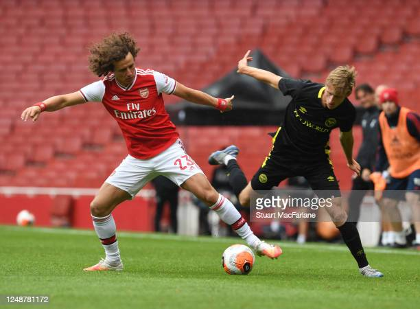 David Luiz of Arsenal challenges Henrik Dalsgaard of Brentford during a friendly match between Arsenal and Brentford at Emirates Stadium on June 10...