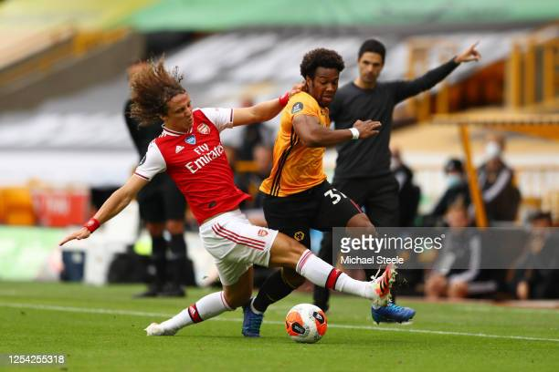David Luiz of Arsenal fouls Adama Traore of Wolverhampton Wanderers leading to receiving a yellow card during the Premier League match between...