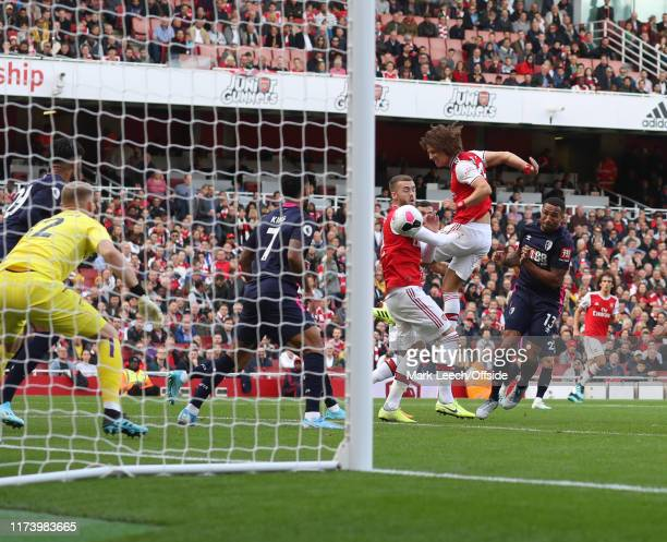 David Luiz of Arsenal gets to the ball before Calum Chambers of Arsenal to head the first goal during the Premier League match between Arsenal FC and...