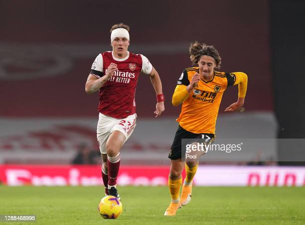 David Luiz of Arsenal runs with the ball whilst under pressure from Fabio Silva of Wolverhampton Wanderers during the Premier League match between...