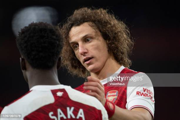 David Luiz of Arsenal talks to team-mate Bukayo Saka during the Premier League match between Arsenal and Newcastle United at Emirates Stadium on...