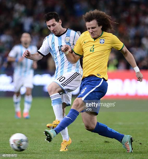 David Luiz of Brazil and Lionel Messi of Argentina battle for the ball during a match between Argentina and Brazil as part of 2014 Super Clasico at...