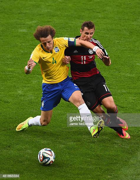 David Luiz of Brazil is challenged by Miroslav Klose of Germany during the 2014 FIFA World Cup Brazil Semi Final match between Brazil and Germany at...